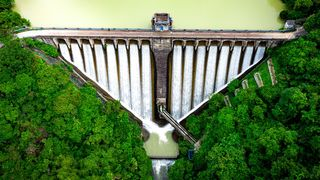A century-old triangular-shaped dam holds back the Kowloon reservoir in Hong Kong… (Credit: Chunyip Wong/Getty Images)