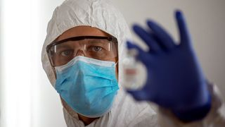 A scientist holding up a vial of Covid-19 vaccine (Credit: Getty Images)