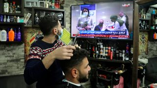 A barber watching Covid-19 news (Credit: Jaafar Ashtiyeh / Getty Images)