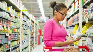 Woman looking at food label (Credit: Getty Images)