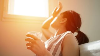 Woman in hot room with glass of water (Credit: Skaman306/Getty Images)